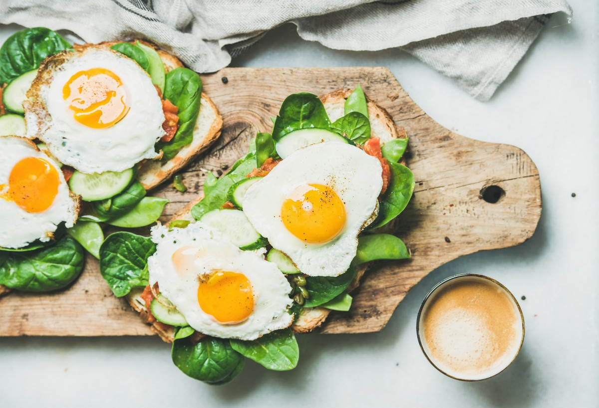 Breakfast toast with sunny-side-up eggs and lots of greens