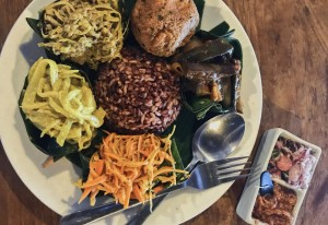 Discover Nasi Campur, in Ubud, Bali. A dish of spicy carrot and banana blossom salads, stir-fried eggplant, coconut curry, ratatouille, garlic infused cauliflower and classic Indonesian greens.