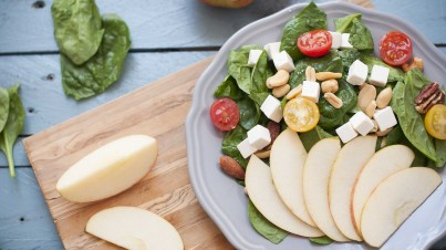 Spinach salad with apple, mixed nuts, and feta