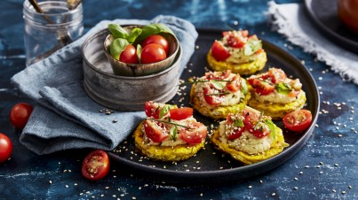 Omelettes (canapes) with hummus, cherry tomatoes and sesame