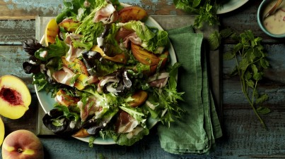 Salade met gegrilde perzik, prosciutto en yoghurt dressing