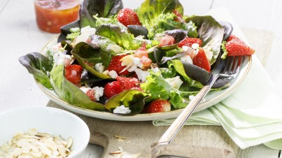 Fresh salad with red butterhead lettuce with strawberries, kale, almonds and goat cheese