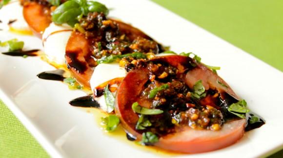 Ensalada caprese de tomate, mozzarella y vinagreta de albahaca y pistachos
