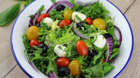 Mediterranean salad with cherry tomatoes, black olives, mozzarella and basil