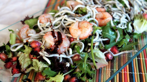Warm salad of mixed lettuce with prawns and pomegranite