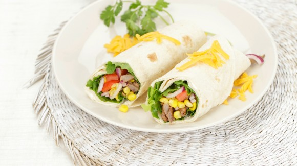 Tortilla wrap with lettuce, beef strips, avocado, tomatoes and Cheddar cheese