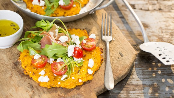 Zoete aardappelpizza met rucola, tomaat en prosciutto